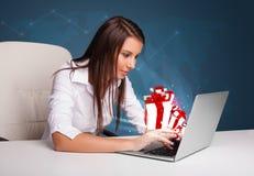 Señora bonita que se sienta en el escritorio y que pulsa en la computadora portátil con actual BO Imágenes de archivo libres de regalías