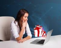 Señora bonita que se sienta en el escritorio y que pulsa en la computadora portátil con actual BO Foto de archivo