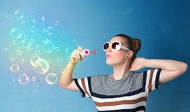 Señora bonita que sopla burbujas coloridas en fondo azul Fotos de archivo libres de regalías