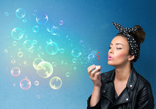 Señora bonita que sopla burbujas coloridas en fondo azul Imagen de archivo