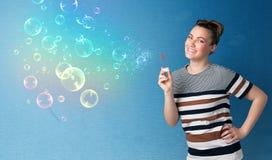 Señora bonita que sopla burbujas coloridas en fondo azul Imágenes de archivo libres de regalías