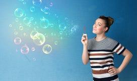 Señora bonita que sopla burbujas coloridas en fondo azul Fotografía de archivo libre de regalías
