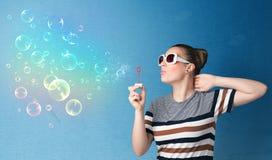 Señora bonita que sopla burbujas coloridas en fondo azul Fotografía de archivo