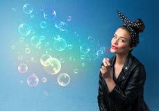Señora bonita que sopla burbujas coloridas en fondo azul Imagenes de archivo