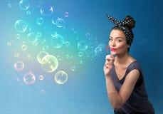 Señora bonita que sopla burbujas coloridas en fondo azul Foto de archivo