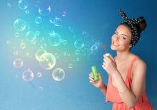 Señora bonita que sopla burbujas coloridas en fondo azul Imagen de archivo libre de regalías
