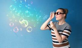 Señora bonita que sopla burbujas coloridas en fondo azul Foto de archivo libre de regalías