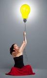 Señora bonita que sostiene un globo de la bombilla Fotos de archivo libres de regalías