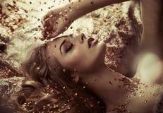 Señora bonita que toma un baño cristalino de oro foto de archivo libre de regalías