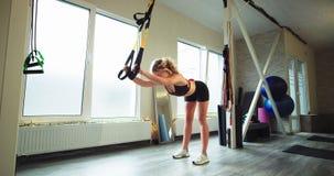 Señora carismática y concentrada en un estudio aerobio que estira el cuerpo mientras que usa a bandas elásticas de las correas un metrajes
