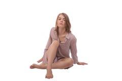 Señora caucásica de Saxy con el pelo rubio, llevando en la camisa que se sienta en la tierra Aislado en el fondo blanco Imagen de archivo