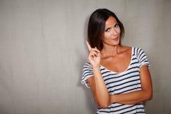 Señora caucásica joven que se coloca con el finger aumentado Fotografía de archivo