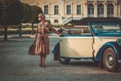 Señora cerca del coche clásico Foto de archivo libre de regalías