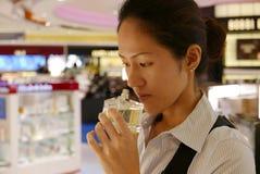 Señora china asiática que evalúa su compra adentro con franquicia Foto de archivo