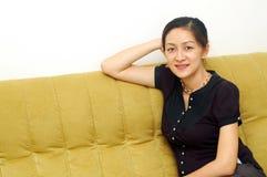Señora china On Sofa imagen de archivo
