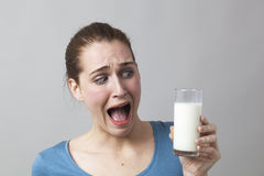 Señora chocada que sostiene el vidrio de leche con el pelo atado detrás Fotos de archivo libres de regalías