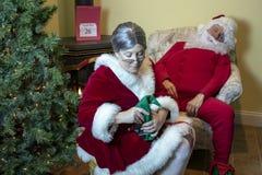 señora Claus que da masajes a los pies cansados de Papá Noel fotos de archivo libres de regalías