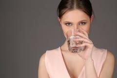 Señora con el agua potable del maquillaje Cierre para arriba Fondo gris Imagen de archivo libre de regalías
