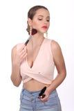 Señora con el cepillo del maquillaje que mira abajo Cierre para arriba Fondo blanco Fotografía de archivo libre de regalías