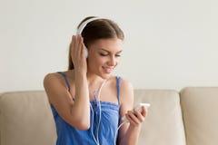 Señora con el teléfono móvil que elige música en tienda en línea Fotografía de archivo libre de regalías