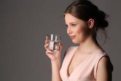 Señora con el vidrio de agua Cierre para arriba Fondo gris Imagen de archivo libre de regalías