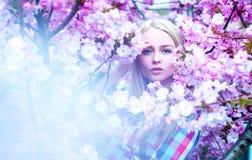 Señora con las flores que miran la cámara El tiempo de primavera… subió las hojas, fondo natural Imagen de archivo libre de regalías
