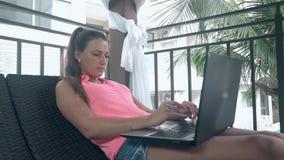 Señora con los trabajos del anillo y de la pulsera de oro sobre el ordenador por las palmas metrajes