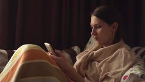 Señora con smartphone en la cama