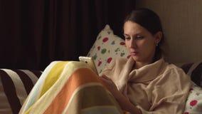 Señora con smartphone en la cama almacen de metraje de vídeo