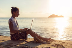 Señora con un ordenador portátil en la playa Fotos de archivo libres de regalías