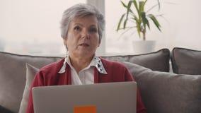 Señora de anciano que habla en la charla video usando su ordenador portátil metrajes