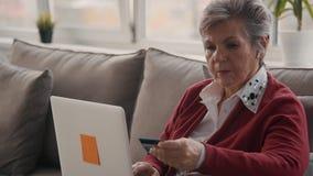 Señora de anciano que usa el ordenador portátil y sosteniendo la tarjeta plástica en sus manos almacen de video