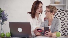 Se?ora de anciano y mujer madurada que hacen compras en l?nea almacen de metraje de vídeo