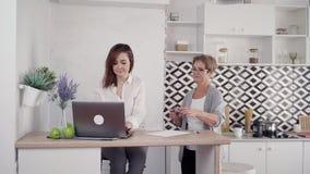 Señora de anciano y mujer madurada que trabajan en casa y té de la bebida almacen de metraje de vídeo