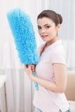 Señora de aspecto joven que presenta con barrido de limpieza Imagen de archivo
