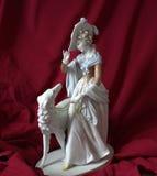 Señora de la estatuilla de la porcelana con el perro contra la perspectiva del terciopelo rojo Imágenes de archivo libres de regalías