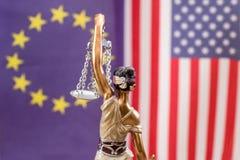 Señora de la justicia contra la bandera de Europa y de los E.E.U.U. imagenes de archivo