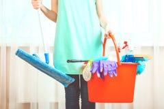 Señora de la limpieza con los productos de una fregona y de limpieza fotos de archivo