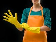 Señora de la limpieza que pone en los guantes de goma Imágenes de archivo libres de regalías