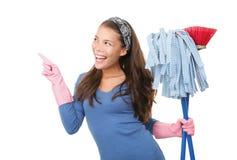 Señora de la limpieza que señala en el fondo blanco