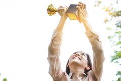 Señora de la oficina que sostiene un trofeo fotos de archivo libres de regalías