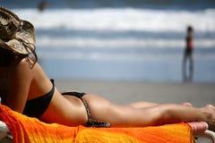 Señora de Latina en el cuerpo que lleva el bikini negro que consigue el baño del sol para broncear en la cama de la playa en la c imagenes de archivo
