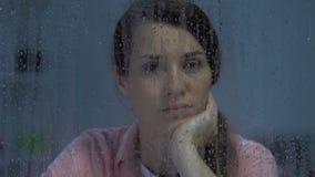 Señora de mediana edad pensativa presionada que mira en la ventana lluviosa, soledad sufridora metrajes