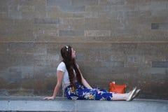 Señora de moda con la corona de la flor que se sienta en la pared imagen de archivo libre de regalías