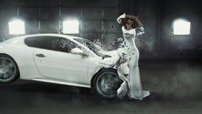 Señora de moda de fascinación en el medio del choque de coche Foto de archivo