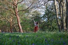 Señora de moda que presenta en una madera inglesa con campanillas y árboles imágenes de archivo libres de regalías