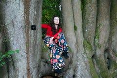 Señora de moda que se sienta en un árbol de haya fotografía de archivo