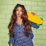 Señora de pelo largo hermosa con un shortboard del penique del color cerca de a Fotografía de archivo