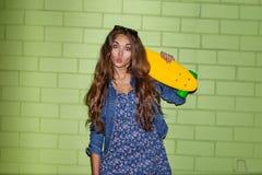 Señora de pelo largo hermosa con un shortboard del penique del color cerca de a Imagen de archivo