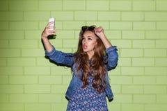 Señora de pelo largo hermosa con un smartphone cerca de un ladrillo verde Imagen de archivo libre de regalías